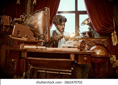 Steampunk world. Intelligent steampunk man scientist inventing something in his laboratory. Victorian interior.