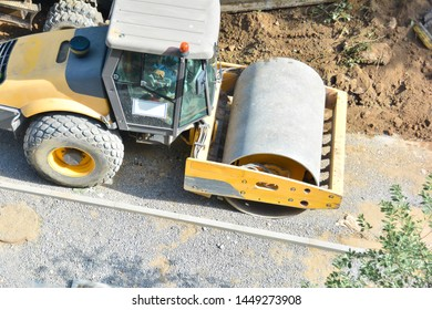 Steamroller performing leveling work on a road under construction. Equipment for construction and repair roads. Yellow steamroller on the street