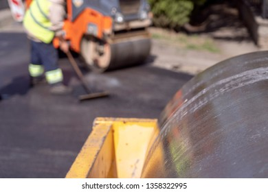 Steamroller and Road Construction Workers at Road Construction Site. Tarmac Laying Works at a Road Construction Site. Hot Asphalt Gravel Leveled by workers. Steamroller Compressing Hot Asphalt.
