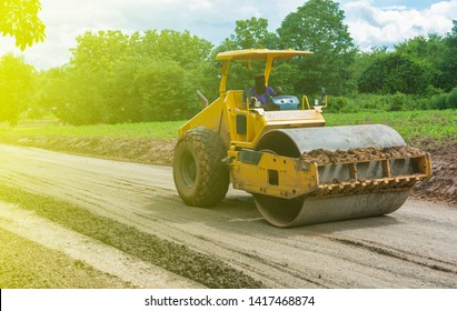 Steamroller or  road roller performing leveling work on a road under construction. Equipment for construction and build new roads. Yellow steamroller on the street - Image