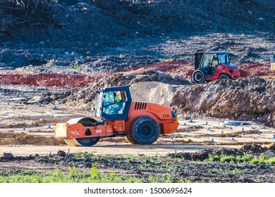 Steamroller working in a large construction site with earth removed. Forklift in the background.
