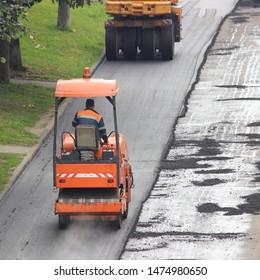 Steamrollers laying of asphalt in city area, industrial machinery - orange asphalt roller on summer day, rebuilding of the road, worker people