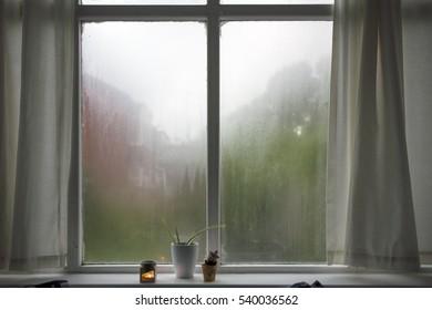 Steamy bedroom window, curtains drawn. Bedroom interior