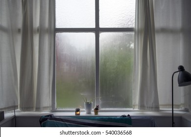 Steamy bedroom window, curtains drawn. Bedroom interior, lamp