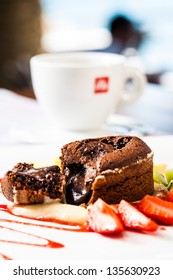 a steamy lava cake broken open served with fresh fruit and coffee