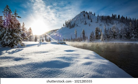 Steamy Madison river flows by its snow covered banks in Yellowst