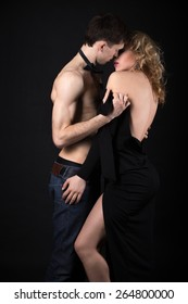 Steamy scene, beautiful sexy young couple foreplay, half naked man in jeans and bow tie taking off his lady evening dress after posh party, studio, black background