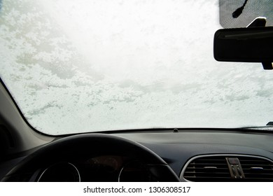 Steamy and snow covered windshield on a winter day.