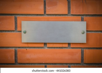 steel or aluminum company name plate with brick wall background or building name plate.