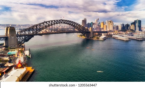 Steel arch of the Sydney harbour bridge over Sydney harbour between North Shore and the city CBD landmarks around the Rocks and Barangaroo.