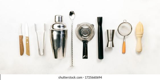 Steel bar tools and accessories for making cocktail. Shaker, jigger, strainer, spoon, tongs, muddler. Alcohol drink and beverages preparation concept. White background, top view, copy space
