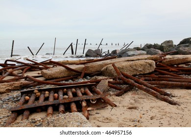 Steel barriers and concrete slabs form coastal defences which have been crushed by nature  to allow the sea to erode the coast of Norfolk, England