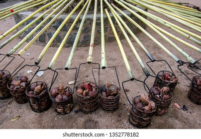 Steel baskets filled with coconut shells and carried on poles ready to be set alight during the Buddhist Esala Perahera (great procession).