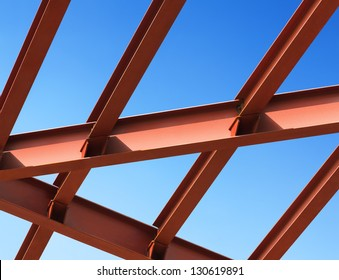 Steel beams against the blue sky. Fragment construction site.