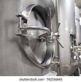 Steel beer brewing tank hatch in a brewery