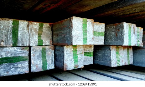 Steel billets square shaped butt ends with painted green vertical and horizontal stripes. Rows of metal cargo storage closeup. Construction industry background. 3D industrial rough metal texture.