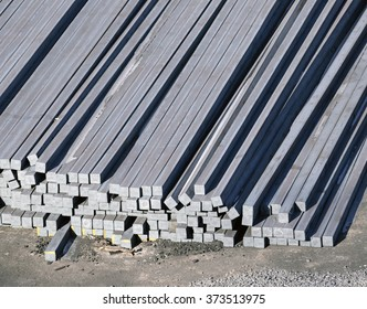 steel billets stacked to loading on a ship in port
