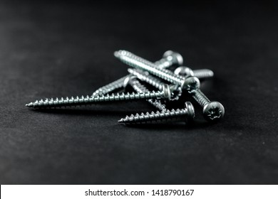 Steel bolts grouped on a black background, threaded screws plated, chromed. Tools for DIY.
