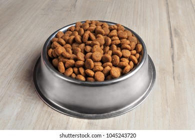 Steel bowl with dog food on wooden floor. Perspective view.