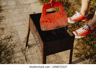 Steel brazier, mangal in camping place. Resting man swings smoke over the brazier