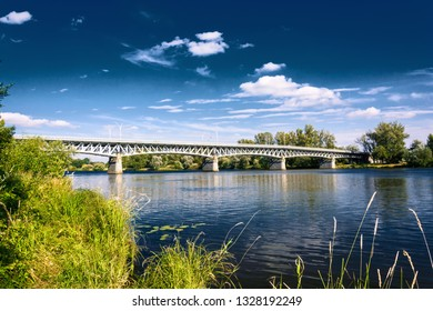Steel bridge across the river Elbe in the town of Litomerice in the Czech Republic. Bridge in summer sunny day. Metal construction of arched bridge with pillars over the river. Architectural monument.