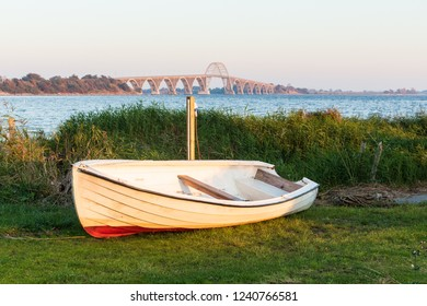 steel bridge to Island of Moen in Denmark with a small wooden boat lying at grassland in the foreground
