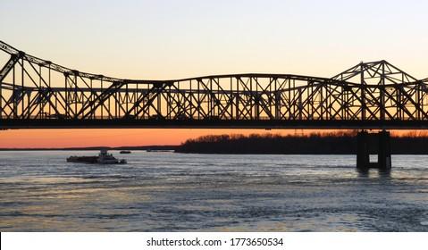 A steel bridge spans the Mississippi River at sunset in Vicksburg, Mississippi.
