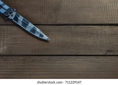 Steel butterfly knife  on a wooden background