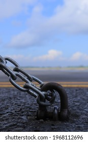 A steel chain is attached to a metal hook on the asphalt with blue sky background