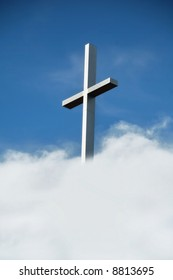 steel Christian cross against blue sky and clouds