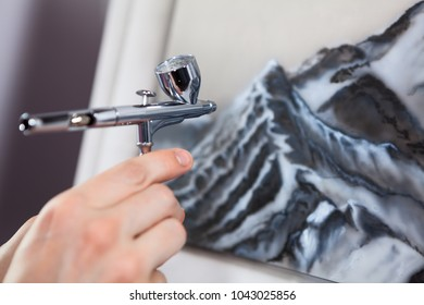 Steel chrome airbrush device in human hand, painting with aerograph, close up view