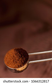 steel coffee spoon with ground coffee on brown background