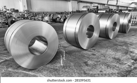 Steel coils inside industrial shed.