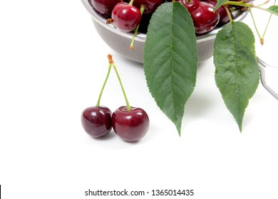 Steel colander with ripe berries of red sweet cherry and several berries in front of the colander. Composition on a white background.