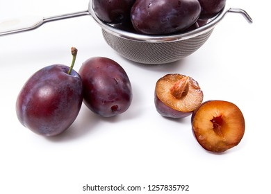 Steel colander with sweet juicy plums, whole and half ripe plums with leaf in front of the colander isolated on a white background.