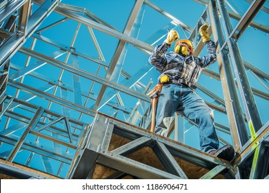 Steel Construction House Building and the Caucasian Contractor with Walkie Talkie in Hand. Skeleton Frame System. Industrial Theme.