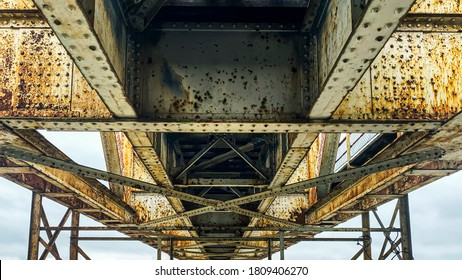 Steel construction of the old unused long train bridge. Close up capture of  the rusty and destroyed structure. Pori Finland