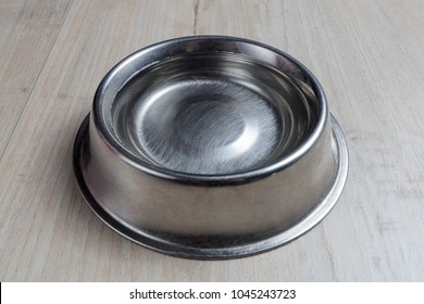 Steel dog bowl with water on wooden floor. Perspective view.