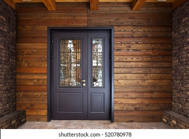 steel door to the house with a wall made of wood and bricks