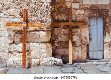 A steel door and two big christian wooden crosses lean against stone wall of the Church of the Holy Sepulchre in Old City of Jerusalem, Israel. Via dolorosa. Jesus christ