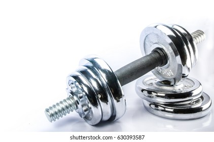 Steel dumbbell for exercise to build muscle on white background.