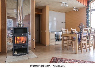 steel fireplace with glass door in wooden cottage with decoration and panoramic windows and glass entrance door.
