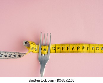 Steel fork with a measuring tape, diet or healthy eating concept