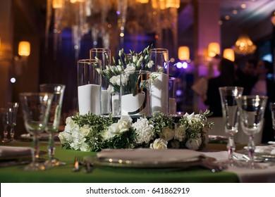 Steel forks lie beneath white plate on green dinner table