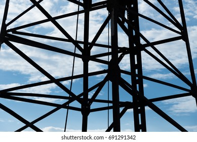 Steel frame of piling machine against blue sky background.
