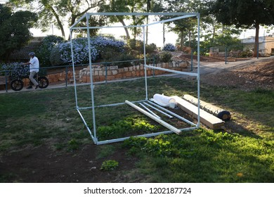 "The steel frame of a ""Sukkah,: a temporary hut used on the Jewish holiday of Sukkoth, being bult outdoors"