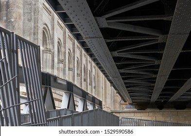 Steel girders and beams of a train trestle contrast with adjacent stone architecture of columns and arches in this urban landscape shot.  Berlin, Germany.  August 2019.