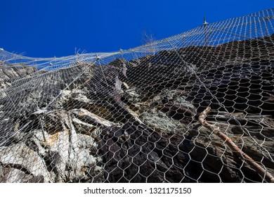 Steel grid over a rockface. Rockfall security net.