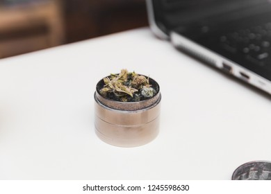 Steel grinder with green cannabis flower (buds) inside. Laptop in background.