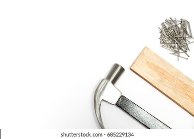 Steel hammer, wooden plate And a pile of nails isolated on white background and have copy space.